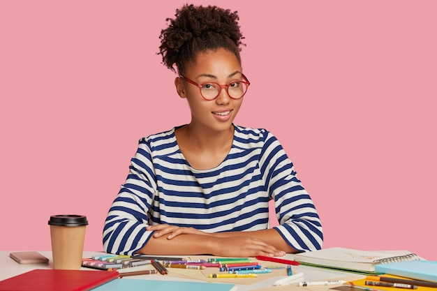 Un Artiste Ou Illustrateur Adolescent Créatif Porte Des Vêtements Décontractés, S'inspire Du Dessin, Entouré De Cahiers Et De Marqueurs Colorés Photo gratuit