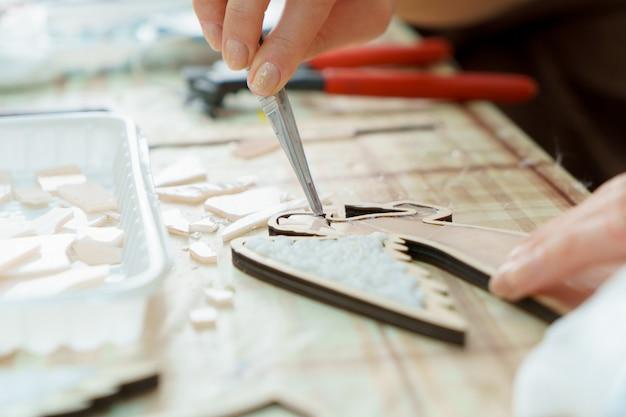 Artiste mains féminines recueillir mosaïque gros plan Photo Premium