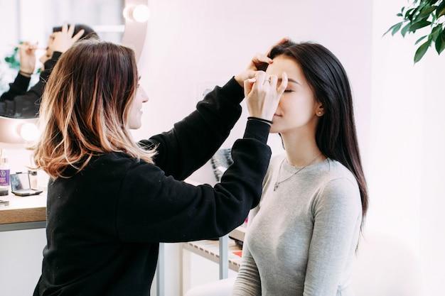 L'artiste de maquillage fait les sourcils de la femme assis devant elle Photo gratuit
