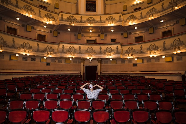 Artiste Mime Féminin Assis Seul Dans Un Auditorium Photo Premium