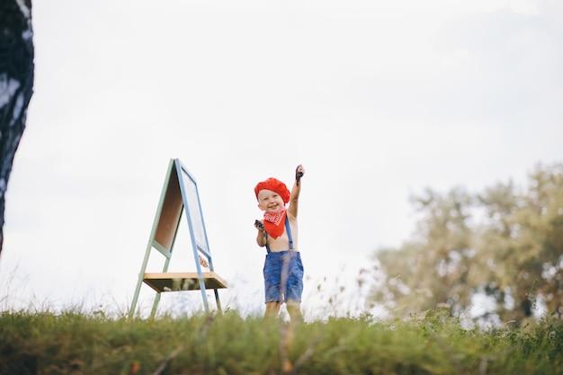 Artiste Peignant Un Paysage D'été. Garçon Sur La Nature De L'artiste Dessine Photo Premium