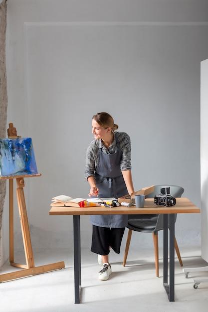 Artiste en tablier travaillant sur un bureau Photo gratuit