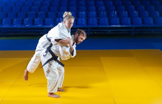 Arts Martiaux. Porteurs épargnants. Sport Homme Et Femme En Kimono Blanc Train Judo Jette Et Capture Dans La Salle De Sport Photo Premium