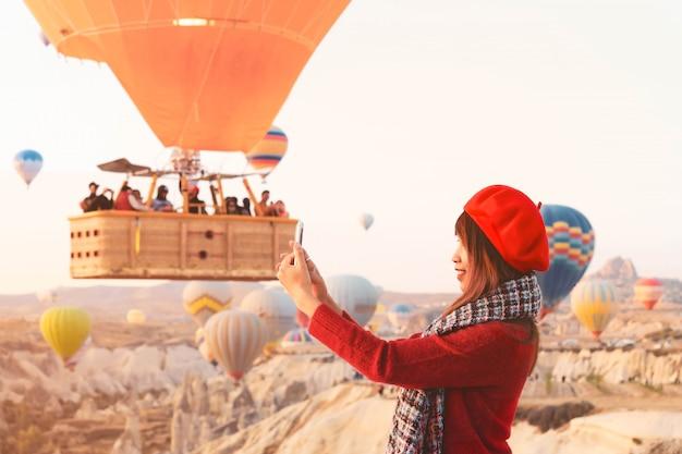 Asain Femme Aime Prendre Des Photos De Ballons à Air Chaud Survolant Le Magnifique Paysage Rocheux De Cappadoce. Photo Premium