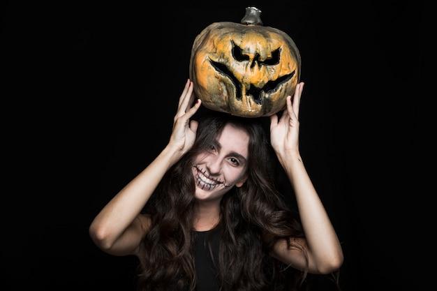 Ashy femme avec citrouille d'halloween au-dessus de la tête Photo gratuit