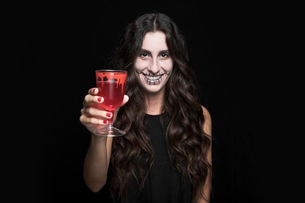 Ashy femme montrant le verre avec du liquide rouge Photo gratuit