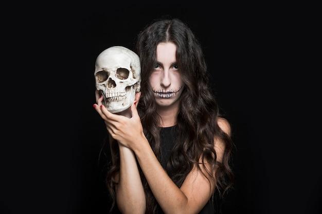 Ashy femme tenant le crâne Photo gratuit