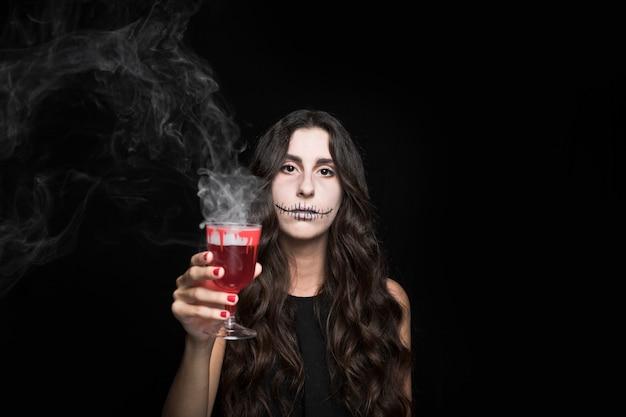Ashy femme tenant le verre avec du liquide brûlant rouge Photo gratuit
