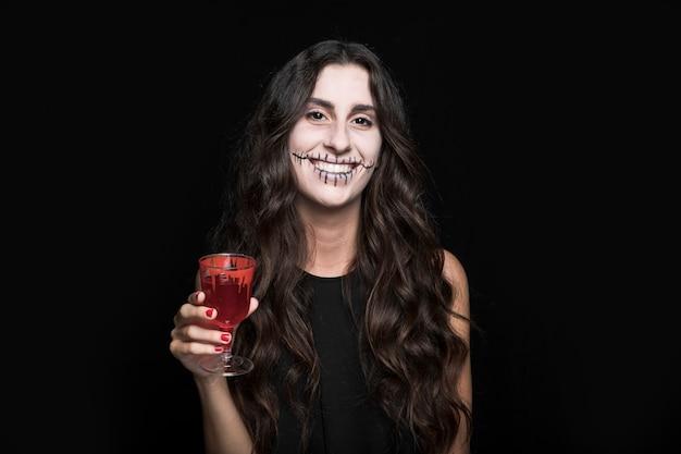 Ashy femme tenant le verre avec du liquide rouge Photo gratuit