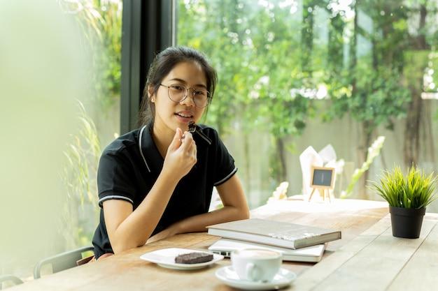 Asiam femme étudiant mange un gâteau avec livre et ordinateur portable au café. Photo Premium