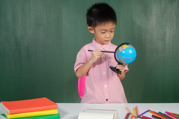 Asian boy pointant sur la carte du monde dans la salle de conseil de craie. Photo Premium