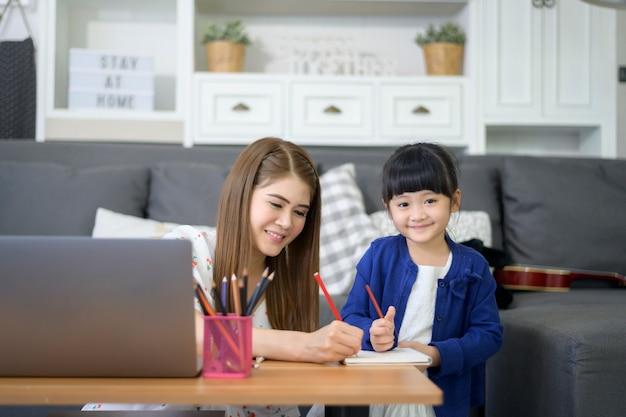 Asian Happy Maman Et Sa Fille Utilisent Un Ordinateur Portable Pour étudier En Ligne Via Internet à La Maison. Concept D'apprentissage En Ligne Pendant La Période De Quarantaine. Photo Premium