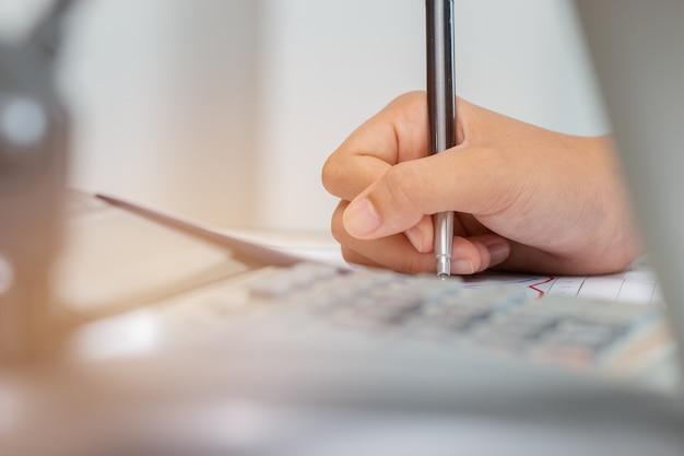 Asian Student Note Sur Un Cahier Tout En Apprenant Une étude En Ligne Ou Un Apprentissage Par Ordinateur Portable Photo Premium