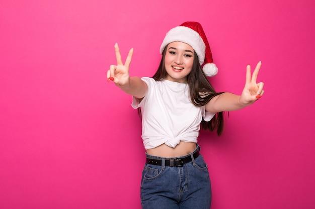 Asian Woman Wearing Santa's Hat Avec Geste De Paix Isolé Sur Mur Rose Photo gratuit
