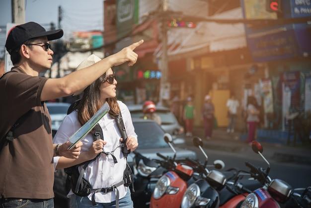 Asiancouple touristique tenant la carte de la ville traversant la route Photo gratuit