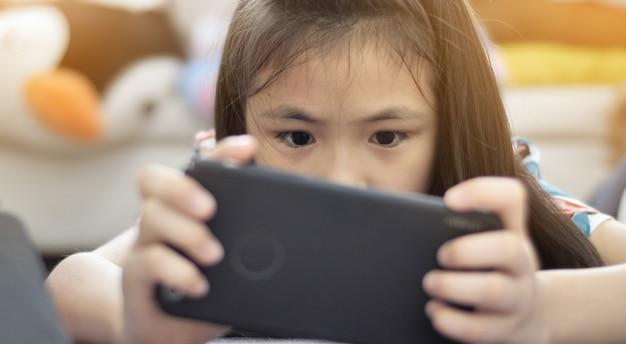 Asiat jouant le jeu sur téléphone portable avec visage souriant. Photo Premium
