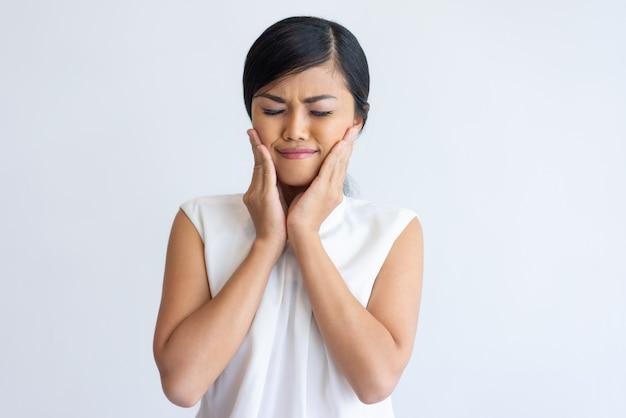 Asiat souriante appréciant l'effet crème pour le visage Photo gratuit