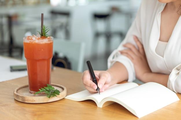 Asiat tenant un stylo noir écrit dans un livre vide. journal écrit des histoires Photo Premium