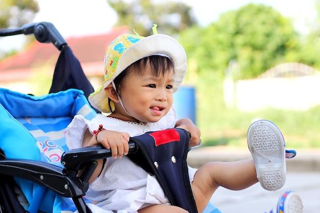 Asiatique bébé enfant fille assise dans une poussette. gamin espiègle. Photo Premium