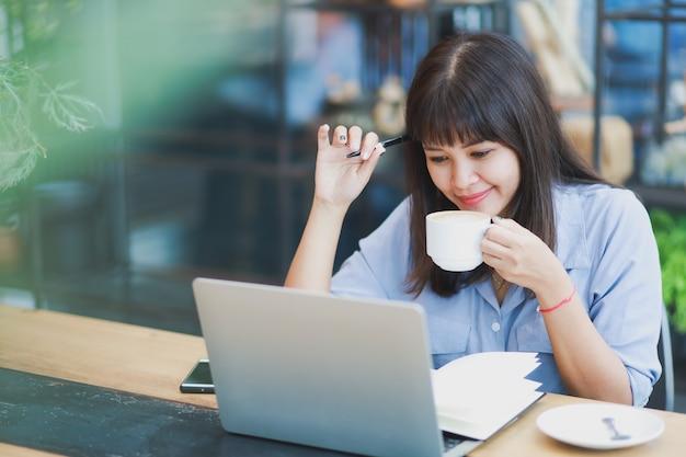 Asiatique belle femme en chemise bleue à l'aide d'ordinateur portable et de boire du café Photo Premium