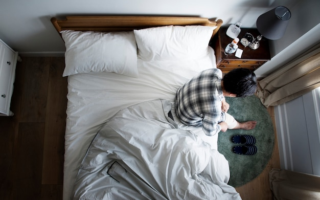 Asiatique blessé assis sur le lit Photo Premium