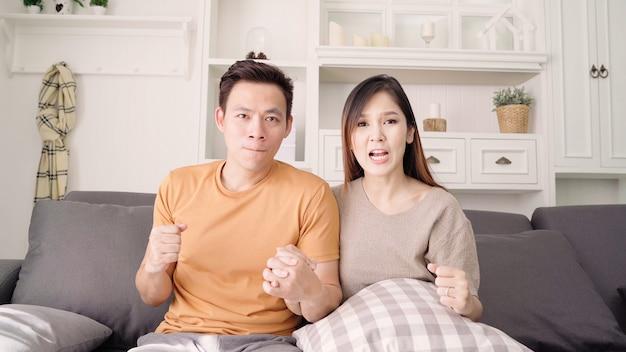 Asiatique, couple, football, match, devant, télévision, salon, chez soi Photo gratuit