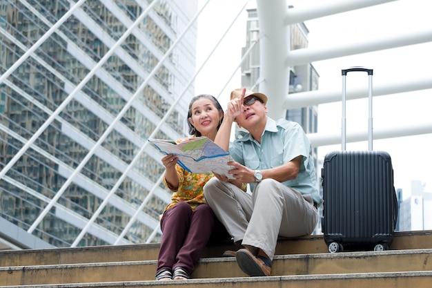 Asiatique couple senior est assis tenant la carte pour rechercher des destinations dans les rues de la grande ville Photo Premium