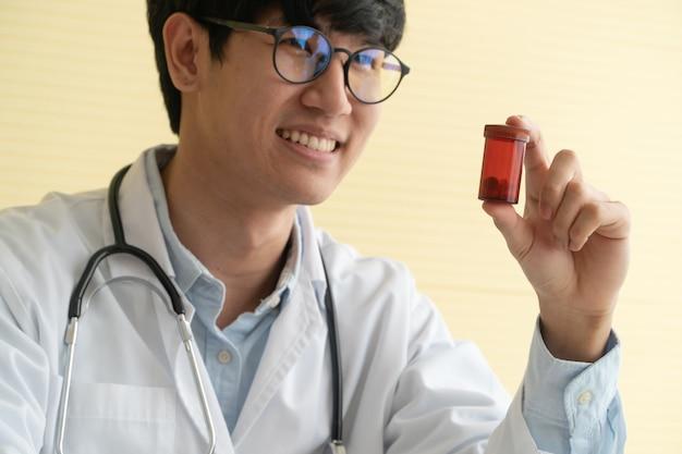 Asiatique docteur avec stéthoscope et uniforme tenant un flacon de médicament Photo Premium