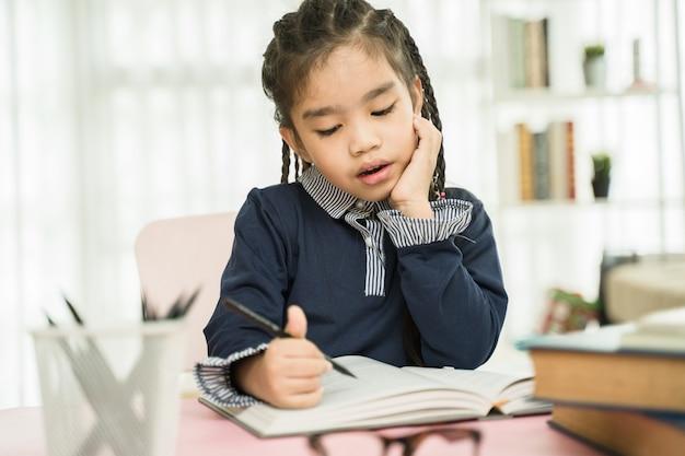 Asiatique élève du primaire étudie ses devoirs à domicile Photo Premium