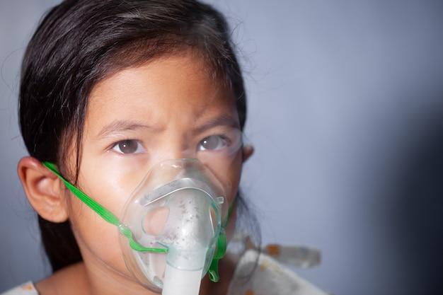 Asiatique enfant fille a besoin de nébulisation par get inhalateur masque sur son visage Photo Premium