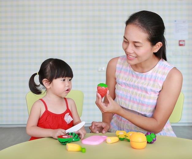 Asiatique enfant fille et mère jouant des fruits en plastique à la chambre des enfants Photo Premium