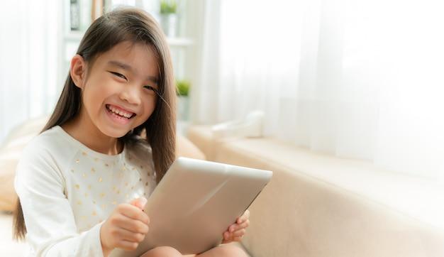 Asiatique enfant mignon, jouer à des jeux avec une tablette et souriant tout en étant assis sur un canapé à la maison Photo Premium