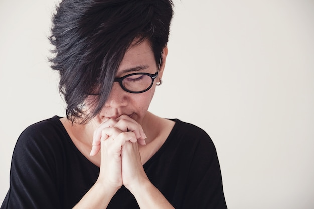 Asiatique femme d'âge moyen porte des lunettes en prière avec les mains ensemble le matin sur un mur blanc Photo Premium