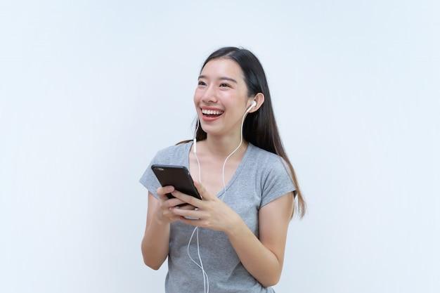 Asiatique femme appréciant sa chanson préférée et sa danse, musique du téléphone mobile Photo Premium
