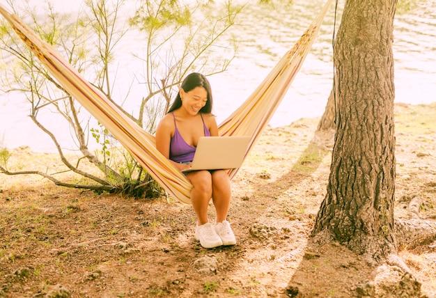 Asiatique femme assise dans un hamac avec ordinateur portable et souriant Photo gratuit
