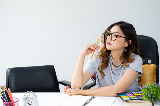 Asiatique femme aux longs cheveux dorés, portant des lunettes, assis au bureau Photo Premium