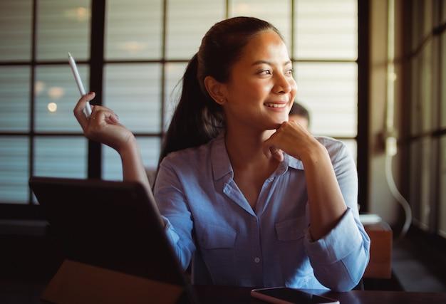 Asiatique femme buvant du café et travaillant avec ordinateur portable au café Photo Premium