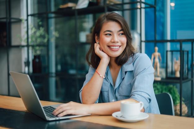 Asiatique femme en chemise bleue au café boire du café et parler avec son petit ami sourire et visage heureux Photo Premium