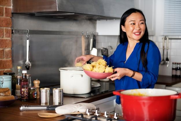 Asiatique femme cuisinant des pâtes dans la cuisine Photo gratuit