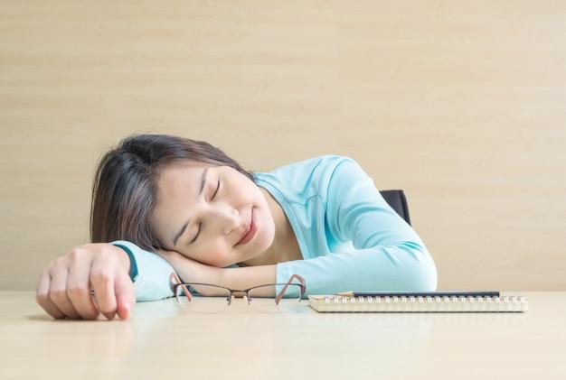 Asiatique femme dormir par menti sur le bureau avec un visage heureux dans le temps de repos du livre de lecture Photo Premium
