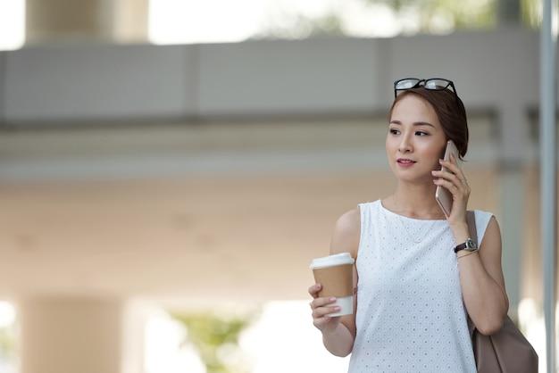 Asiatique, femme, à emporter, café, promenade, rue, parler, téléphone Photo gratuit