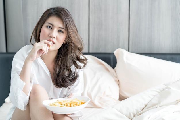 Asiatique femme mangeant des frites Photo Premium