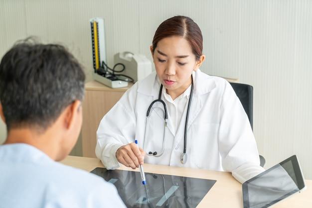 Asiatique femme médecin et patient discutant de quelque chose assis à la table Photo Premium