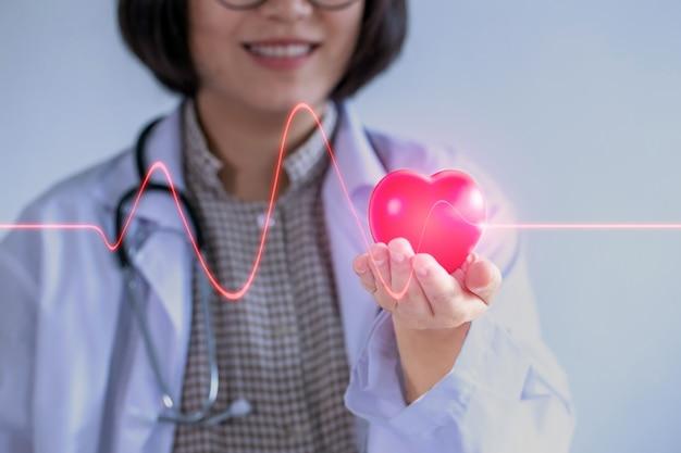 Asiatique Femme Médecin Portant Des Lunettes Tenez Votre Coeur Souriant Amicalement. Photo Premium