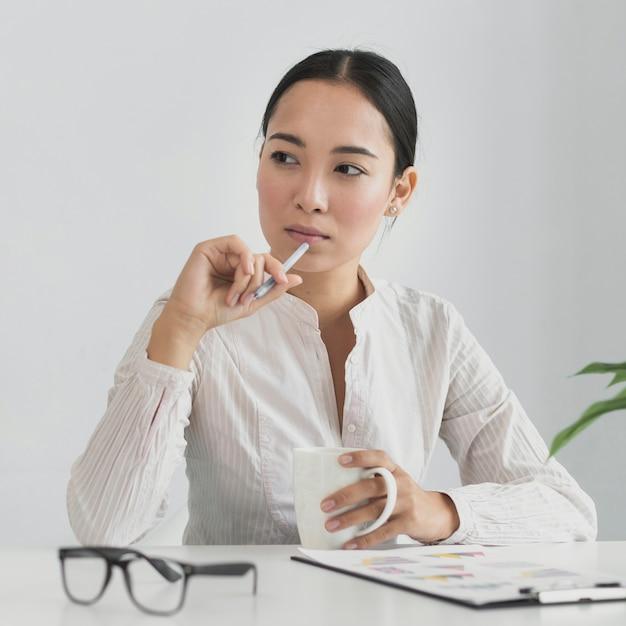 Asiatique femme pensant au bureau Photo gratuit