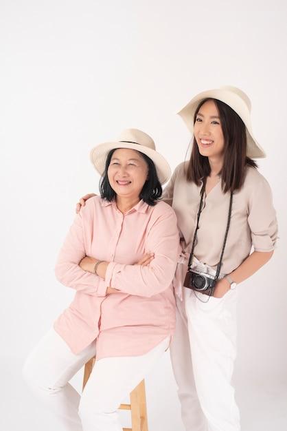 Asiatique Femme Plus âgée Et Sa Fille Sur Mur Blanc, Concept De Voyage Photo Premium
