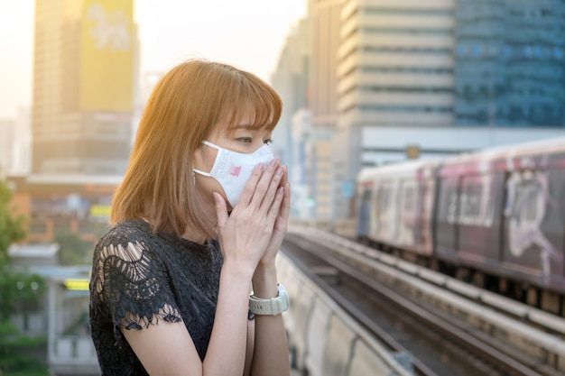 Asiatique femme portant le masque de protection respiratoire n95 contre la pollution de l'air à la gare ferroviaire Photo Premium