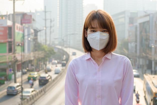 Asiatique femme portant le masque de protection respiratoire n95 contre la pollution de l'air sur les routes et la circulation à bangkok Photo Premium
