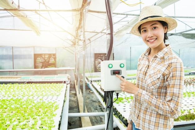Asiatique femme presse sur la machine de contrôle de température dans la serre ferme hydroponique Photo Premium