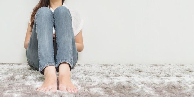 Asiatique femme s'asseoir sur un tapis gris avec ciment blanc fond texturé au coin de la maison avec espace de copie Photo Premium